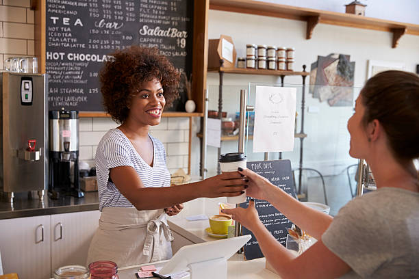 Waitress serving customer over the counter at a coffee shop stock photo