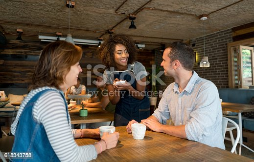 635812444 istock photo Waitress serving customers at a restaurant 618343758