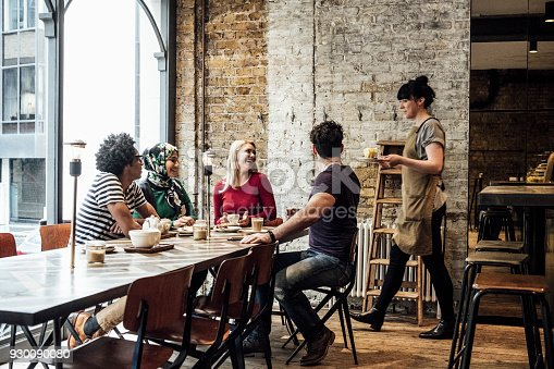 Four friends sitting at table waiting for young woman to bring food and drink