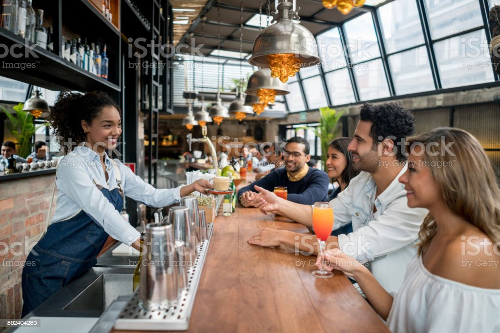 Waitress serving drinks to a group of people at a restaurant stock photo