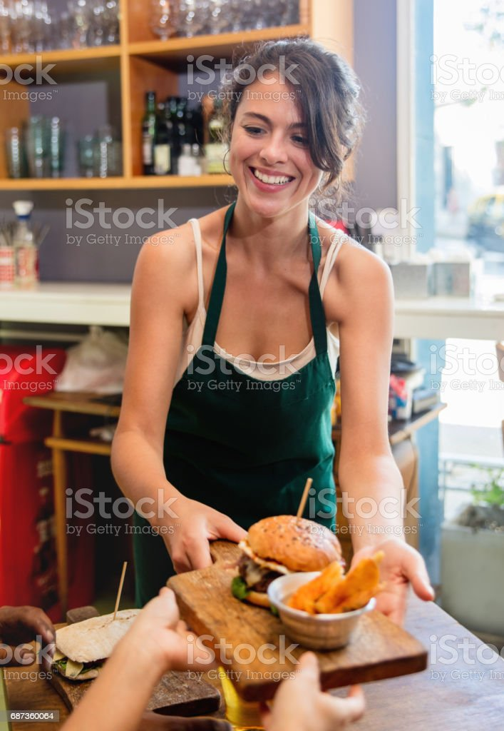 Happy waitress serving food at a fast food restaurant - food service...