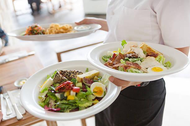 Kellnerin serviert Speisen – Foto