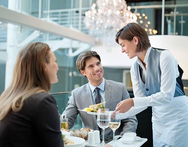 camarera que sirve comida para pareja en el restaurante - gastronomía fina fotografías e imágenes de stock