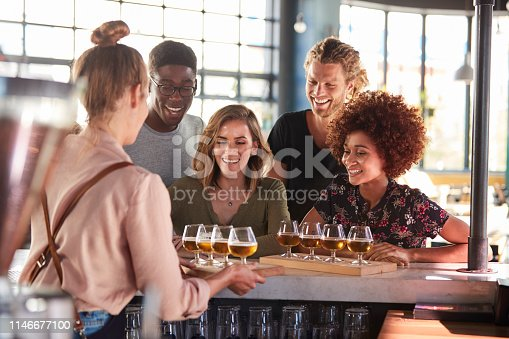 Waitress Serving Group Of Friends Beer Tasting In Bar