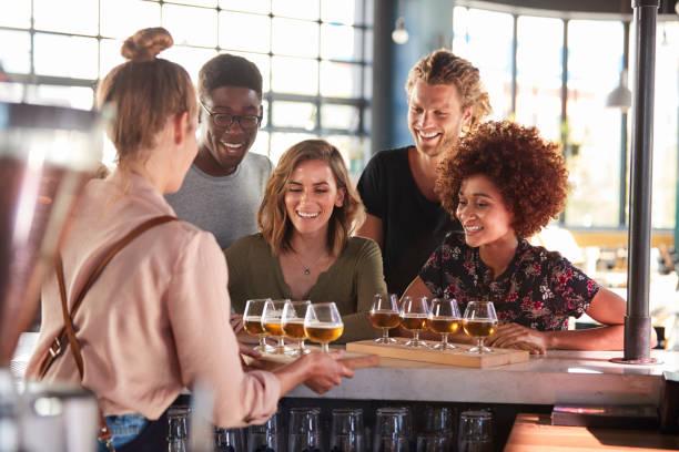 serveerster serveren groep vrienden bierproeverij in bar - tasting stockfoto's en -beelden
