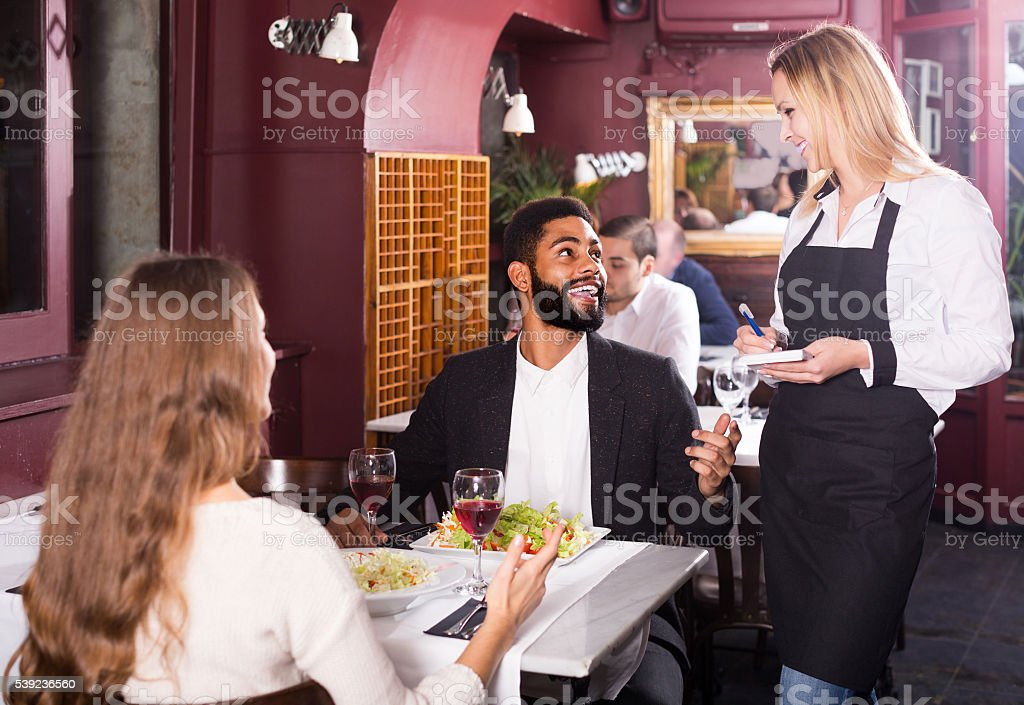 waitress serving meal for young couple at table royalty-free stock photo
