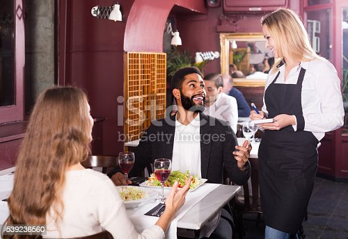 635812444 istock photo waitress serving meal for young couple at table 539236560