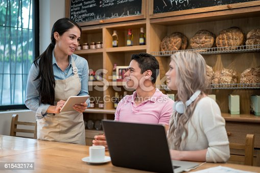635812444 istock photo Waitress serving people at a cafe 615432174