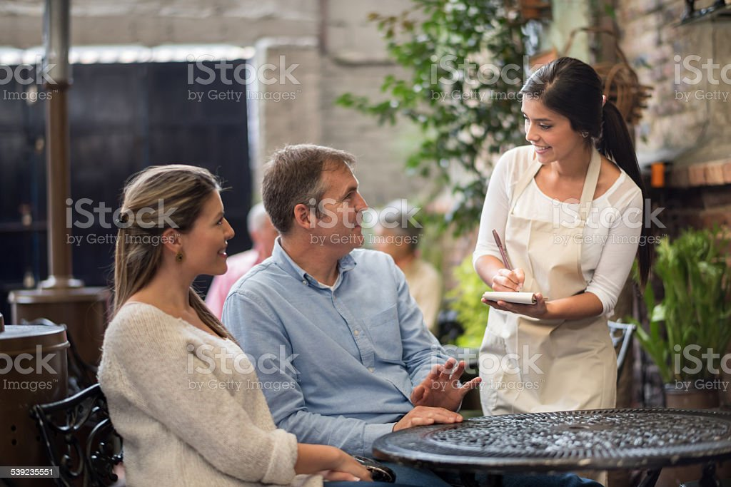 Waitress serving people at a coffee shop stock photo
