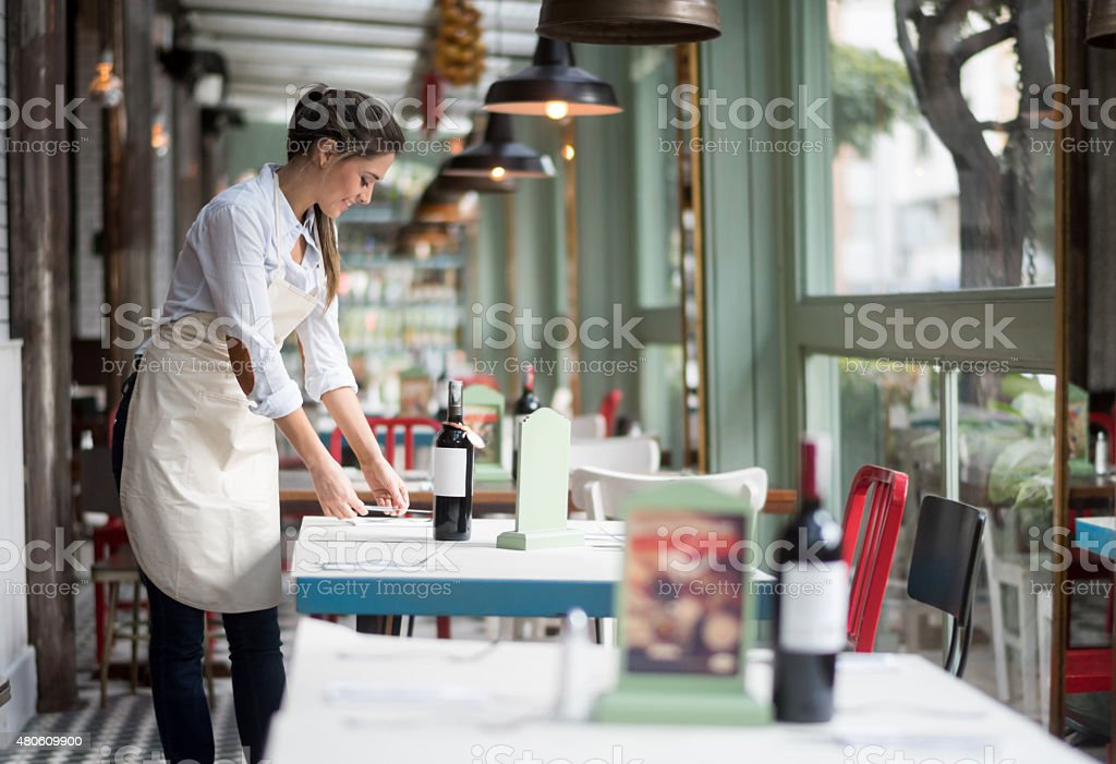 Waitress setting tables at a restaurant stock photo