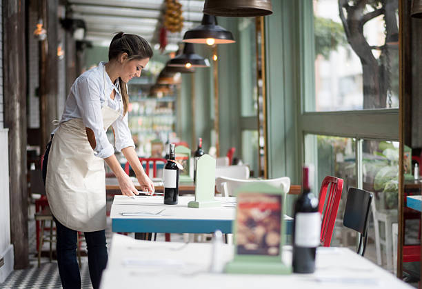 Waitress setting tables at a restaurant Waitress setting tables at a restaurant - food service occupation concepts waiter stock pictures, royalty-free photos & images