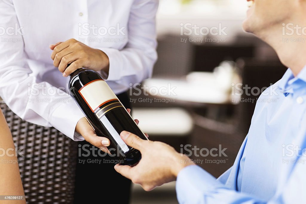 Waitress Showing Red Wine Bottle To Man In Restaurant royalty-free stock photo