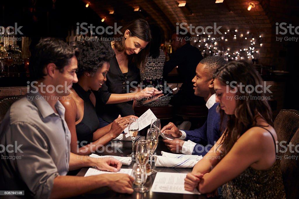 Waitress Takes Order In Restaurant Using Digital Tablet stock photo