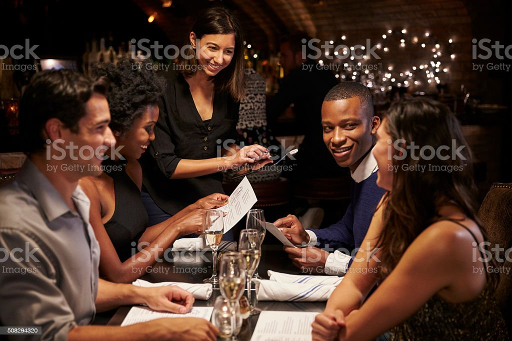 Waitress Takes Order In Restaurant Using Digital Tablet stock photo