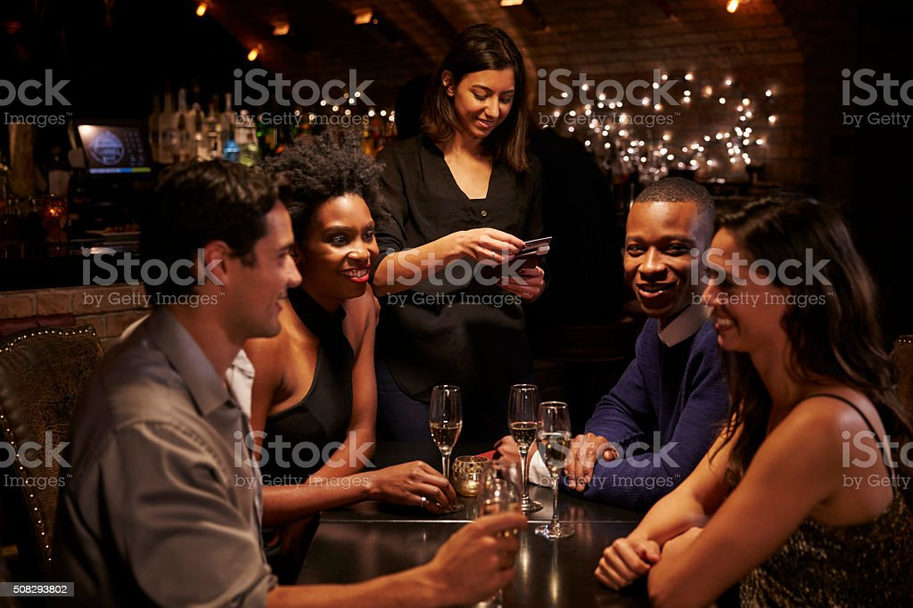 Waitress Takes Payment For Restaurant Bill On Digital Tablet stock photo
