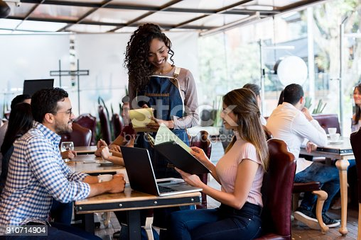 694187664 istock photo Waitress taking an orden from a couple at a restaurant 910714904