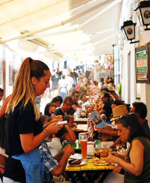 Waitress taking an order at a busy Tapas Bar. stock photo