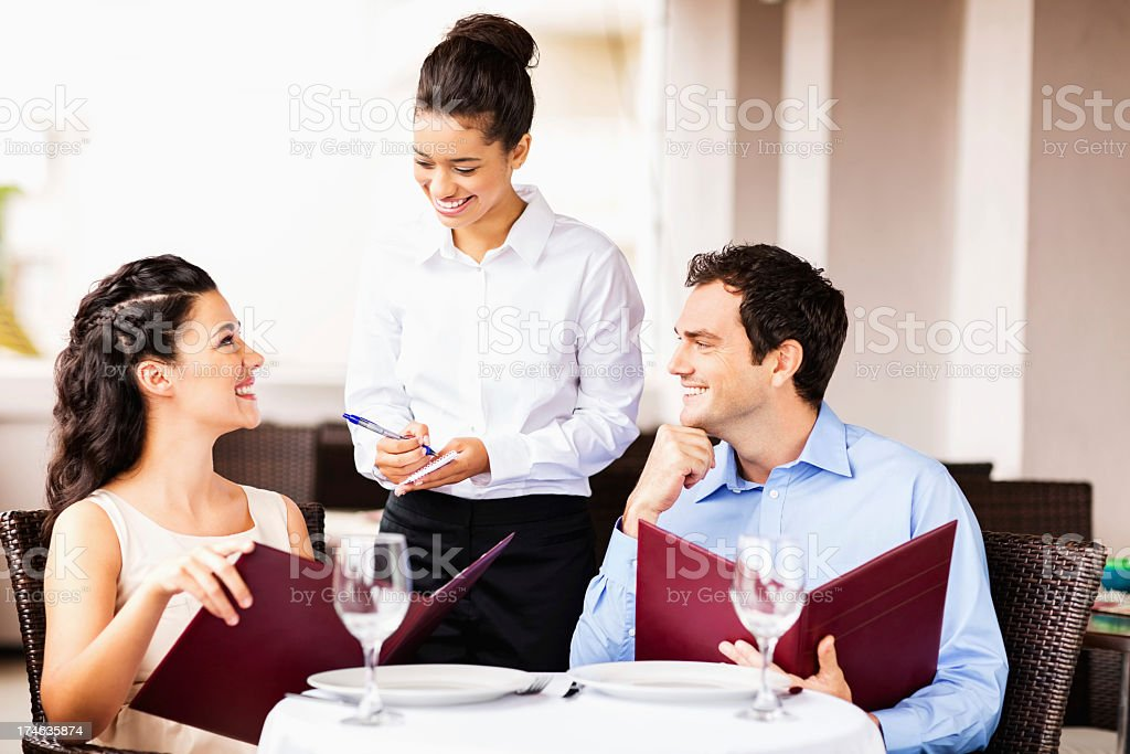 Waitress Taking Order From Couple At Restaurant royalty-free stock photo