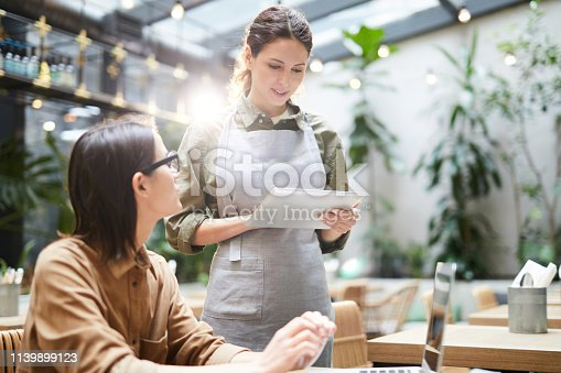 Content attractive waitress in apron standing at table and adding information into tablet while taking order from guest in cafe