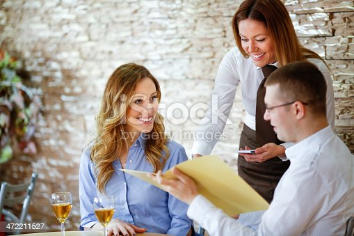 635812444 istock photo Waitress taking order from young couple. 472211527