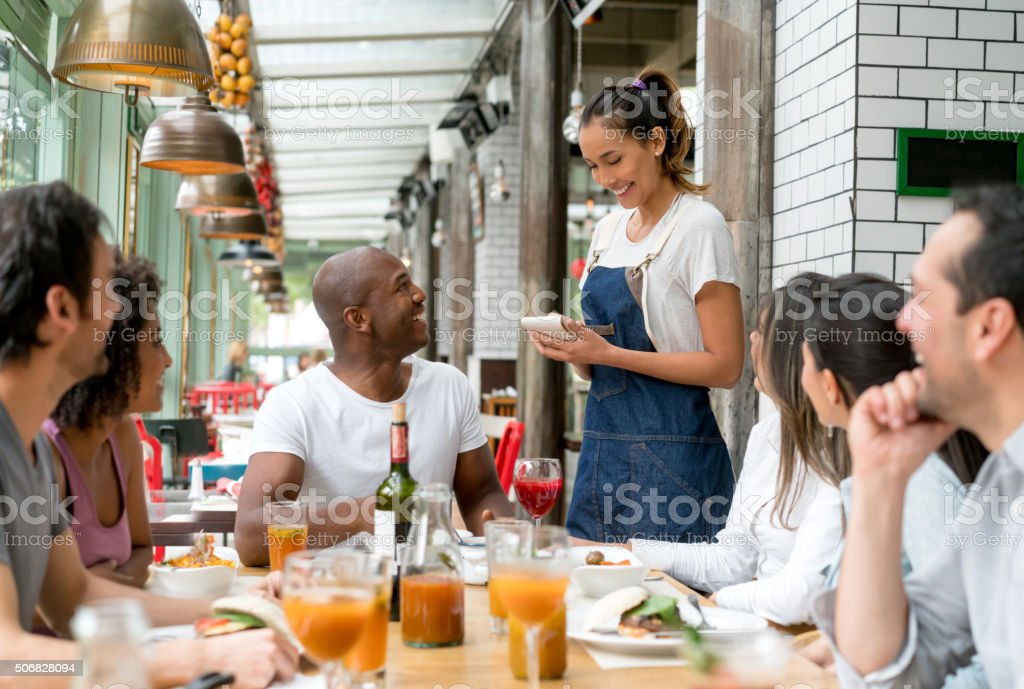 Waitress taking orders to people at a restaurant stock photo