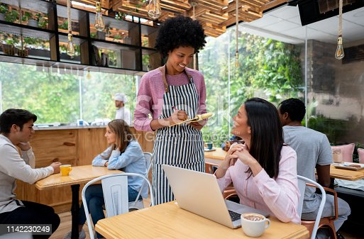 694187664 istock photo Waitress taking the order to a business woman working online at a restaurant 1142230249