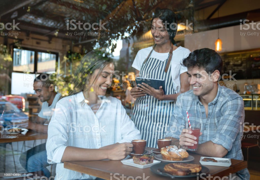 Waitress taking the order to a happy couple at a restaurant stock photo