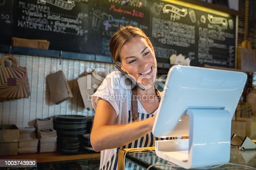 Waitress talking on the phone at a restaurant taking a delivery order and looking happy - food service concepts
