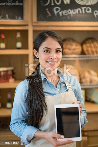 Happy Latin American waitress working at a restaurant and using a tablet computer