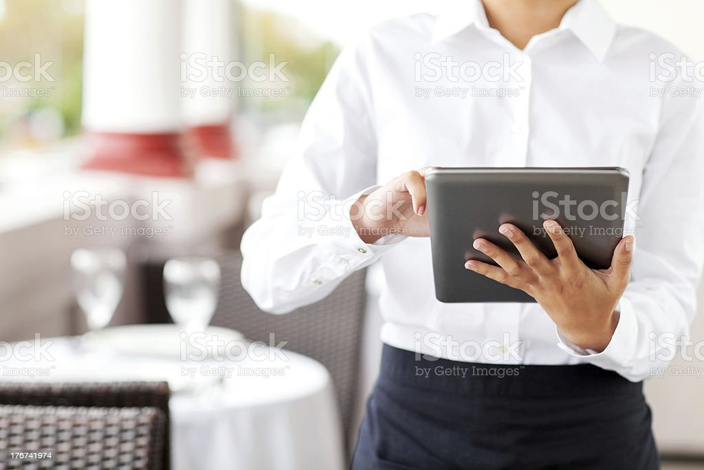 Waitress Using Digital Tablet In Restaurant royalty-free stock photo