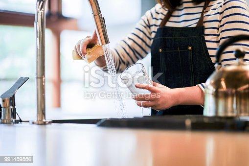 Waitress washing glass in the kitchen of restaurant
