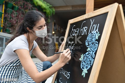 Waitress wearing a facemask while writing the menu at a restaurant on a board during the COVID-19 pandemic – reopening of business concepts