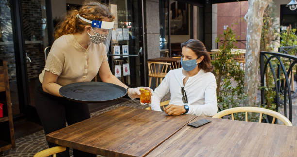 Waitress Wearing PPE During Covid-19 Pandemic Serves Drink to Masked Customer