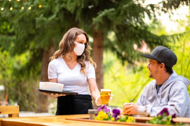 waitress wearing protective equipment for covid - refeições imagens e fotografias de stock