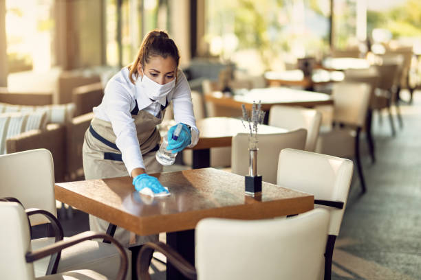 Waitress with a face mask and gloves cleaning tables with disinfectant in a cafe. stock photo