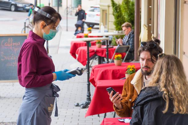 waitress with a mask and clients at an outdoor bar, café or restaurant - covid restaurant imagens e fotografias de stock
