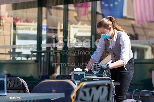 Vilnius, Lithuania - April 30 2020: Waitress with a mask disinfects the table of an outdoor bar, café or restaurant, reopen after quarantine restrictions