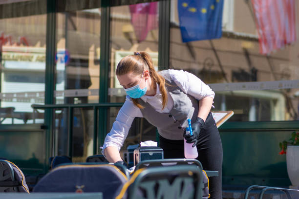 waitress with a mask disinfects the table - covid restaurant imagens e fotografias de stock