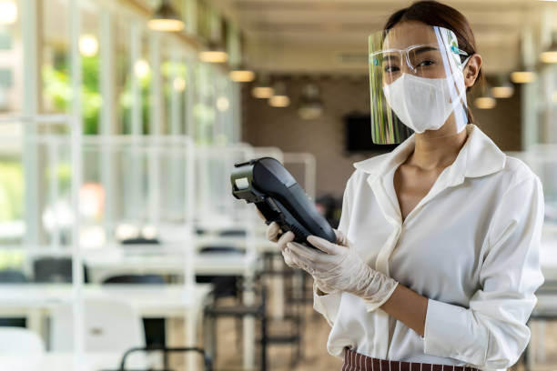 Waitress with face mask hold credit card reader. stock photo