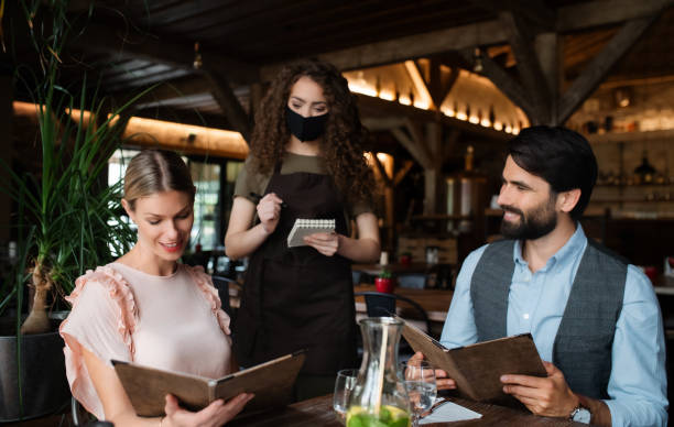Waitress with face mask serving happy couple indoors in restaurant. stock photo