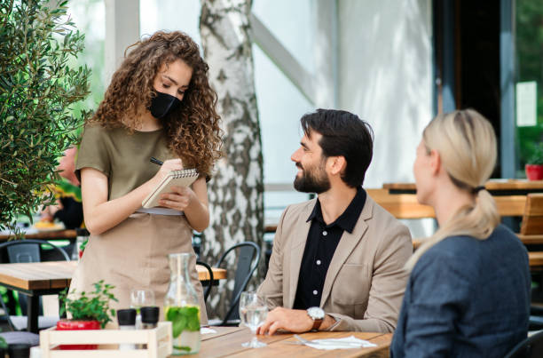 Waitress with face mask serving happy couple outdoors on terrace restaurant. stock photo