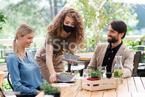 Woman waitress with face mask serving happy couple outdoors on terrace restaurant.
