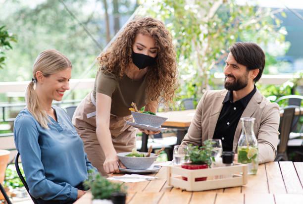 camarera con máscara facial sirviendo feliz pareja al aire libre en el restaurante de la terraza. - couple lunch outdoors fotografías e imágenes de stock