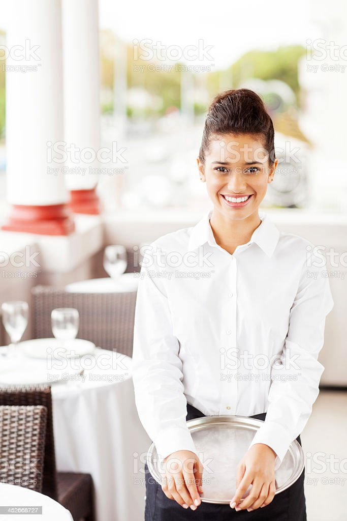 Waitress With Serving Tray Smiling In Restaurant stock photo