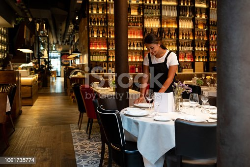 Portrait of a waitress working at a restaurant setting up a table and smiling – food service occupation concepts