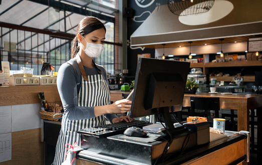 Portrait of a waitress working at a restaurant wearing a facemask and placing the order in the computer - pandemic lifestyle concepts