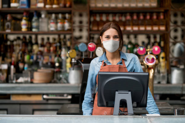 Waitress working at a restaurant wearing a facemask during the COVID-19 pandemic stock photo