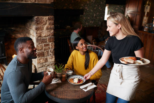 Waitress Working In Traditional English Pub Serving Breakfast To Guests Waitress Working In Traditional English Pub Serving Breakfast To Guests waiter stock pictures, royalty-free photos & images
