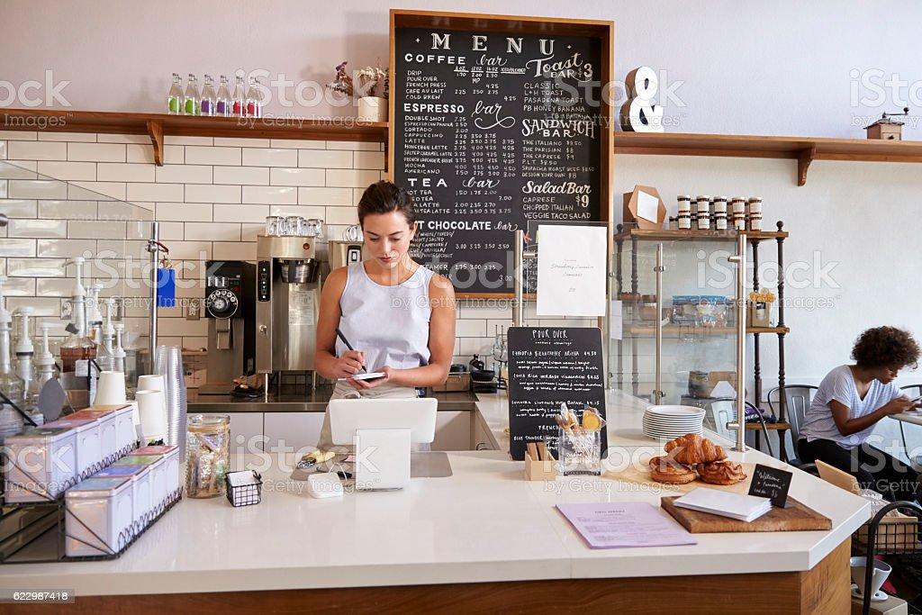 Waitress writing customer's order at counter of coffee shop stock photo