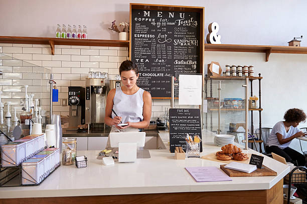 Waitress writing customer's order at counter of coffee shop stock photo